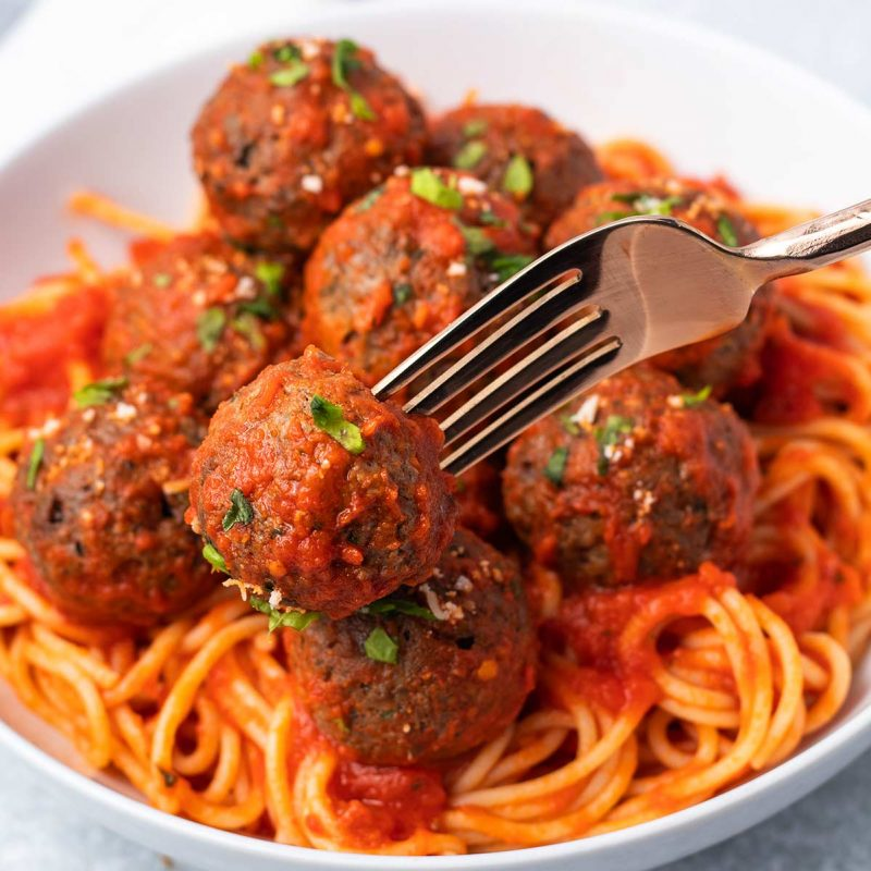 A big bowl of spaghetti and meatballs with a fork picking up one of the meatballs.