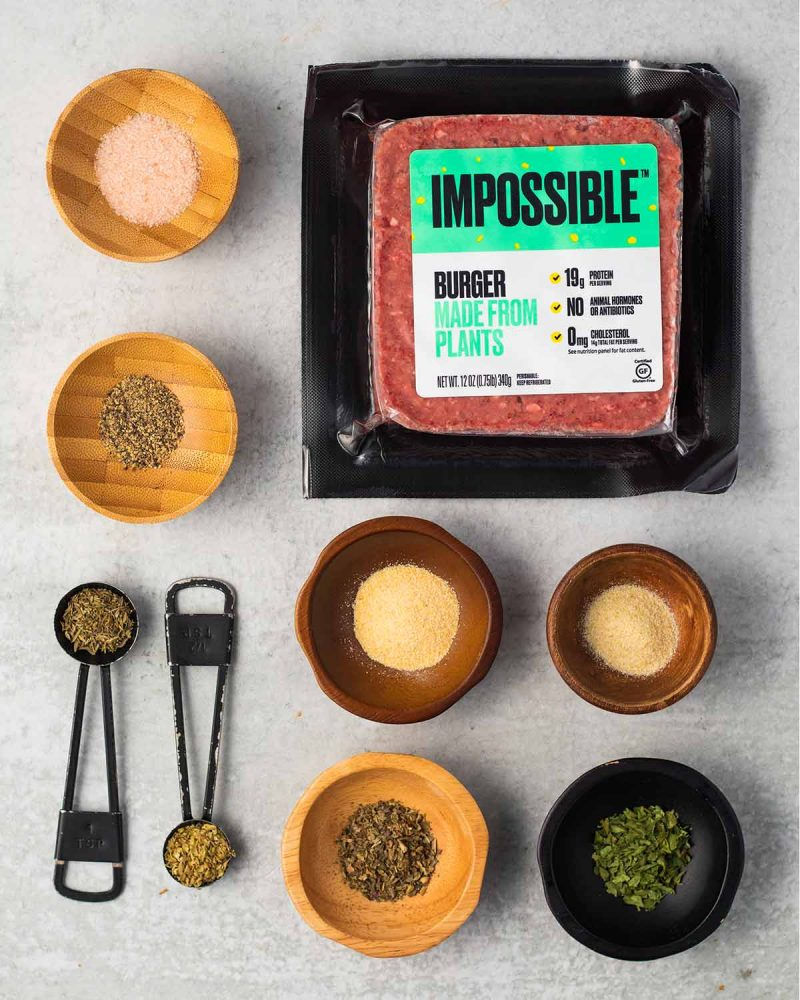 Ingredients for Impossible burger meatballs laid out on a surface. Two measuring spoons with thyme and oregano and 6 tiny bowls with garlic powder, onion powder, basil, parsley, salt, and a pepper alongside a package of the meatless meat.