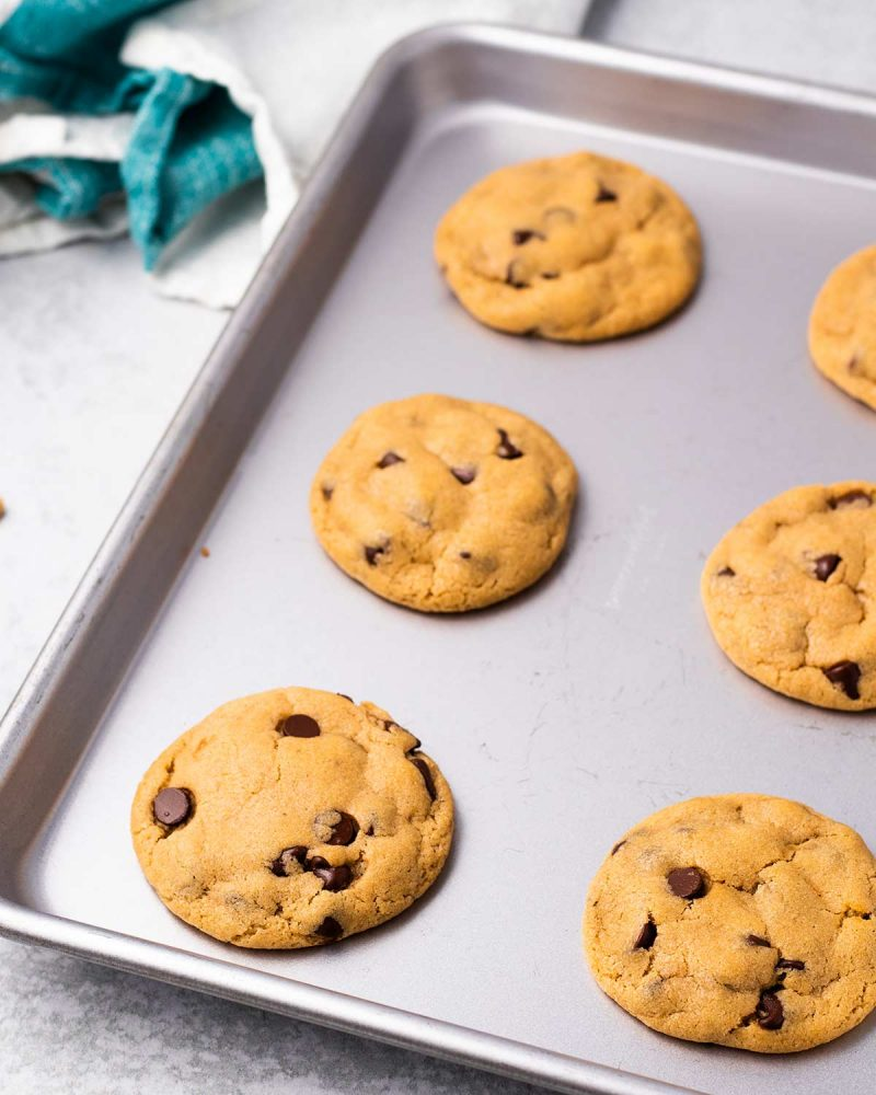 6 baked chocolate chip cookies on a baking sheet.