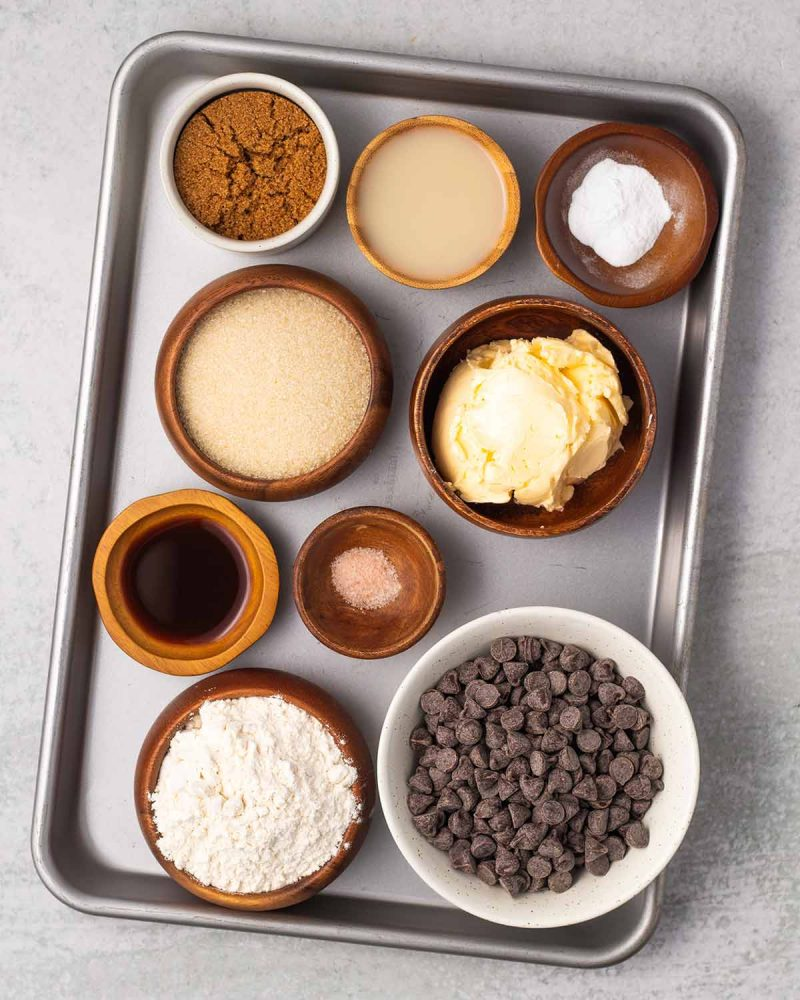 Ingredients for chocolate chip cookies on a baking sheets in small and medium bowls: Brown sugar, non-dairy milk, baking soda, sugar, vegan butter, vanilla extract, salt, flour, and chocolate chips.