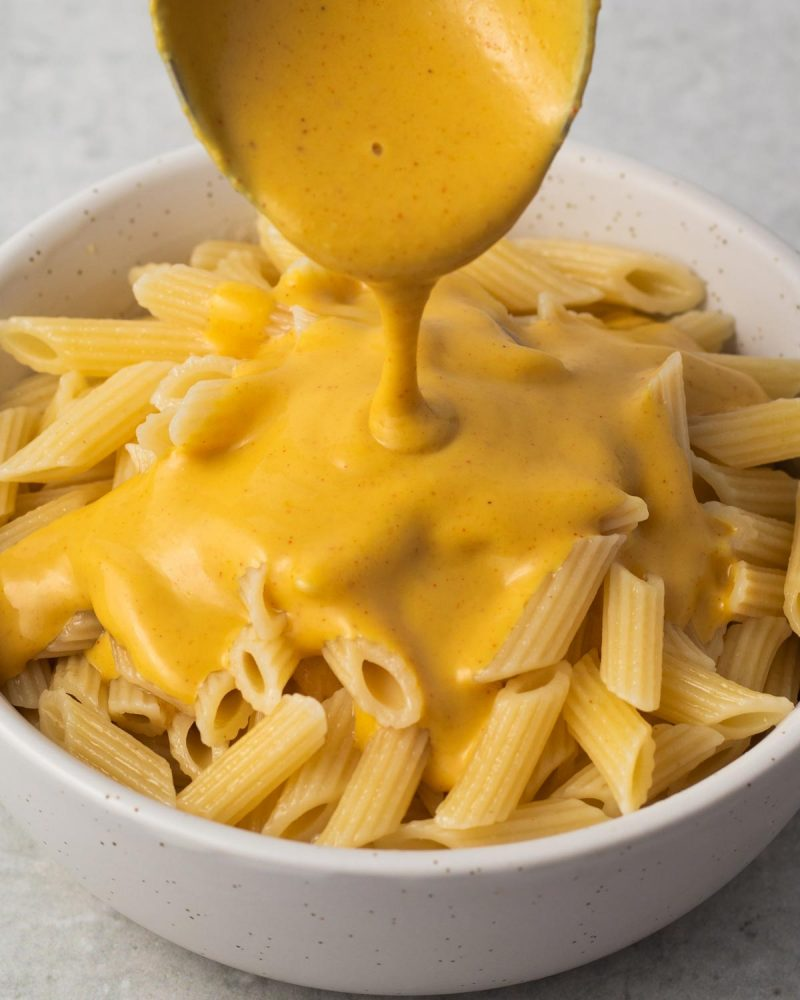 Cheese sauce being poured over mini penne pasta in a bowl.