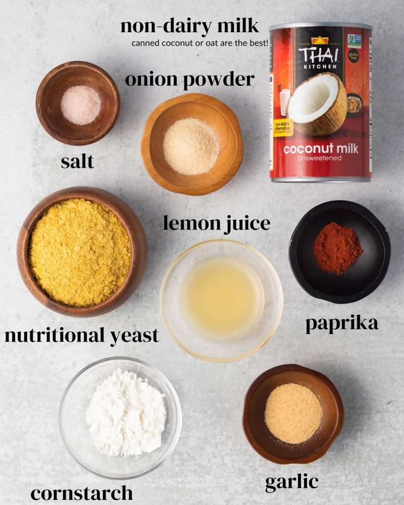 Ingredients laid out on a table: canned coconut milk, salt, lemon juice, onion powder, garlic powder, nutritional yeast, paprika, and cornstarch.