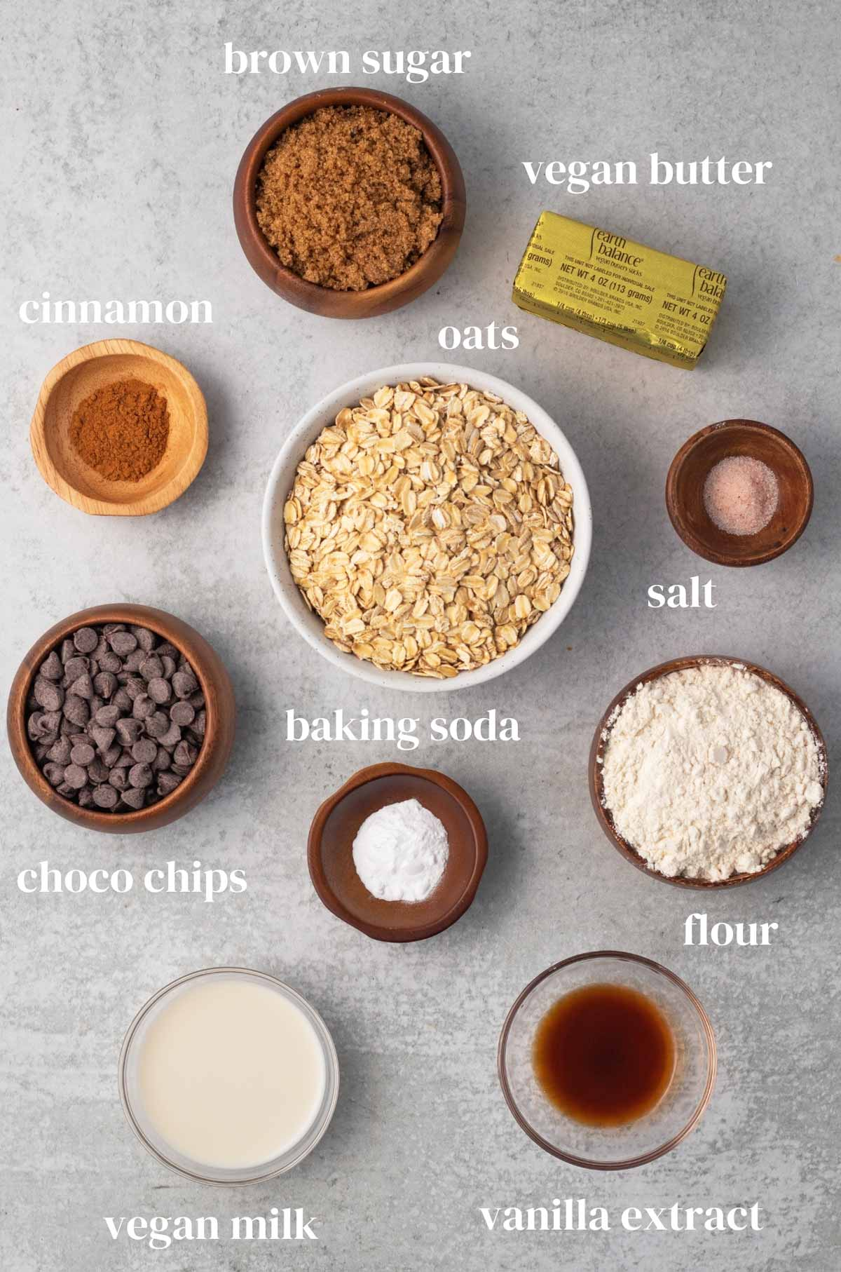 Ingredients laid out on a surface: brown sugar, vegan butter, cinnamon, oats, salt, chocolate chips, baking soda, flour, dairy-free milk, and vanilla extract.