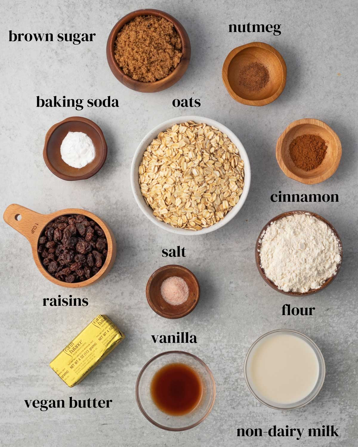 Ingredients laid out on a surface. Brown sugar, nutmeg, cinnamon, baking soda, oats, flour, salt, raisins, vanilla, non-dairy milk and vegan butter.