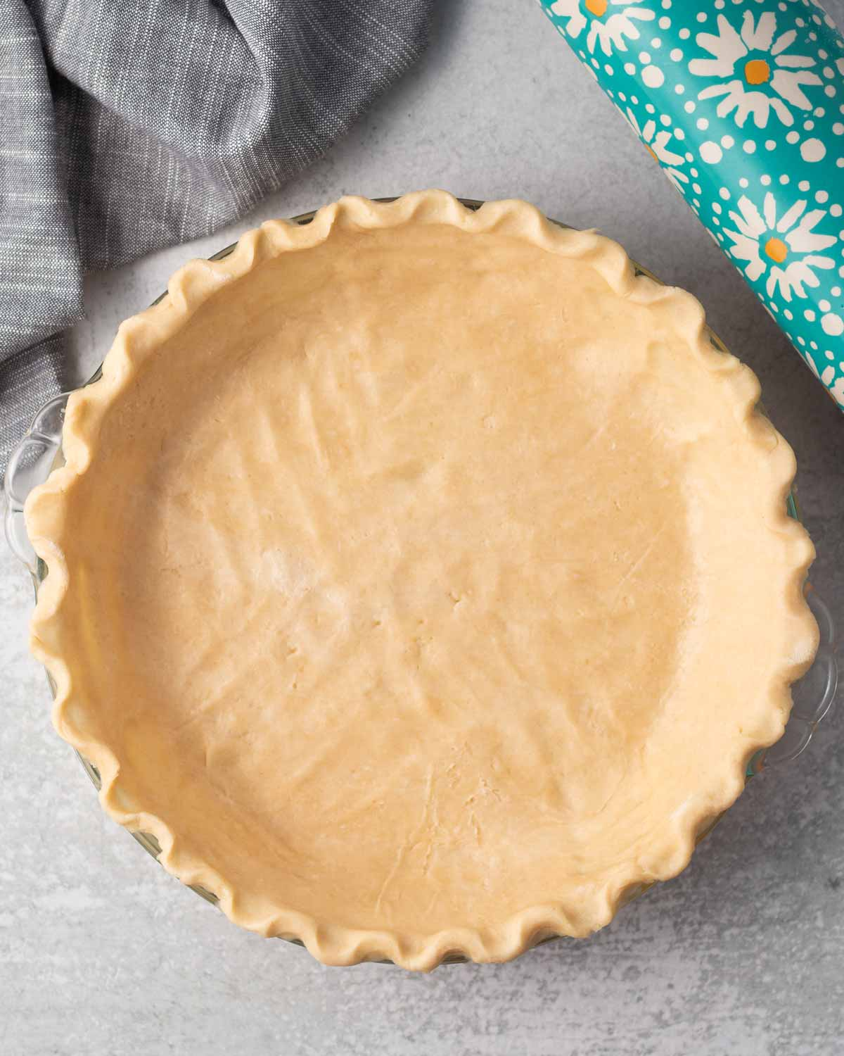 Unbaked pie crust with a scalloped edge. There is a blue rolling pin in the top right corner.
