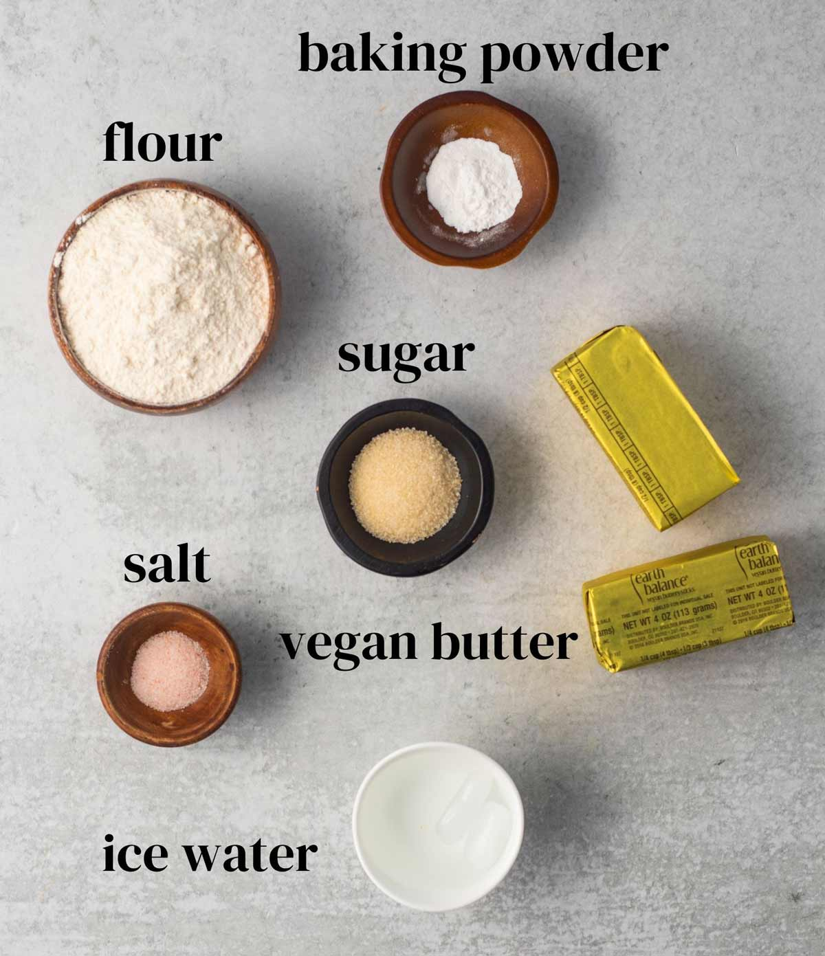 Ingredients laid out on a surface: flour, baking powder, sugar, vegan butter, salt, and ice water.