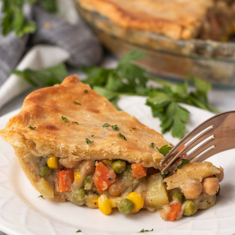 A slice of vegan pot pie on a plate with a fork taking a bite out.