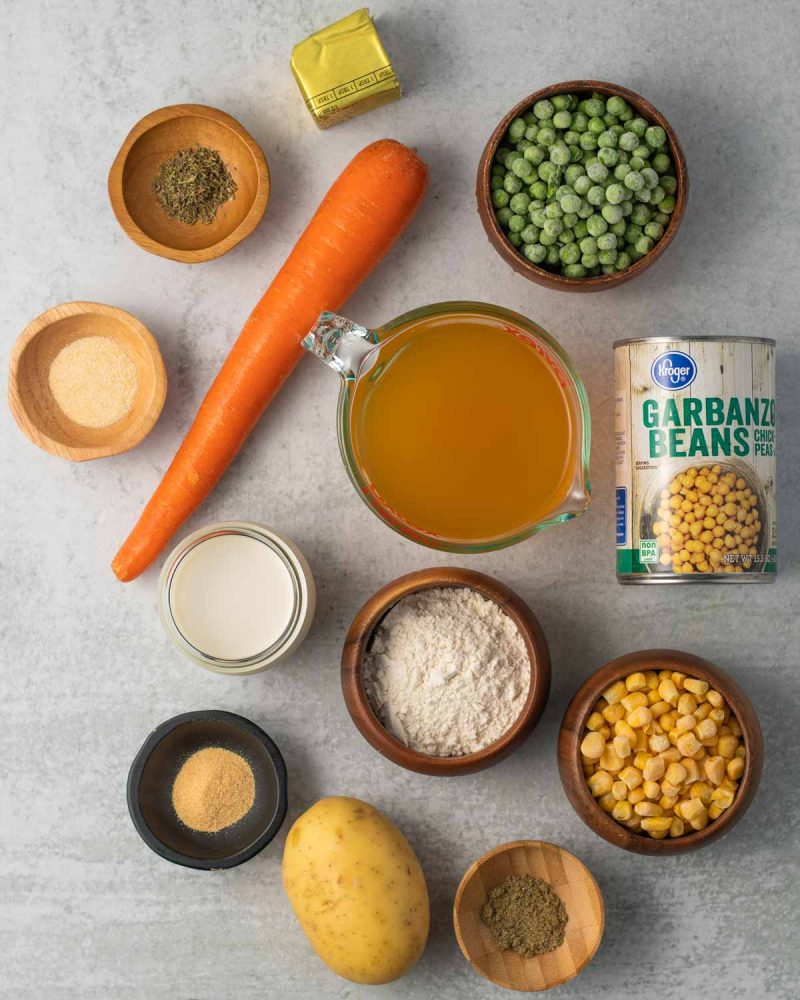 Ingredients laid out on a surface: vegan butter, thyme, sage, garlic powder, onion powder, carrot, frozen peas, frozen corn, flour, oat milk, vegetable broth, potato, and chickpeas.