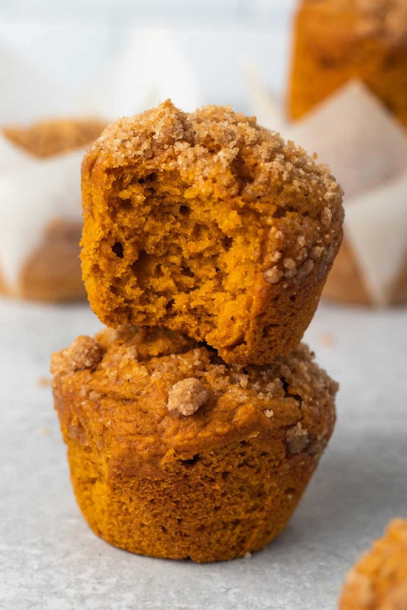 Two vegan pumpkin muffins stacked on each other. The top muffin has a bite taken out.
