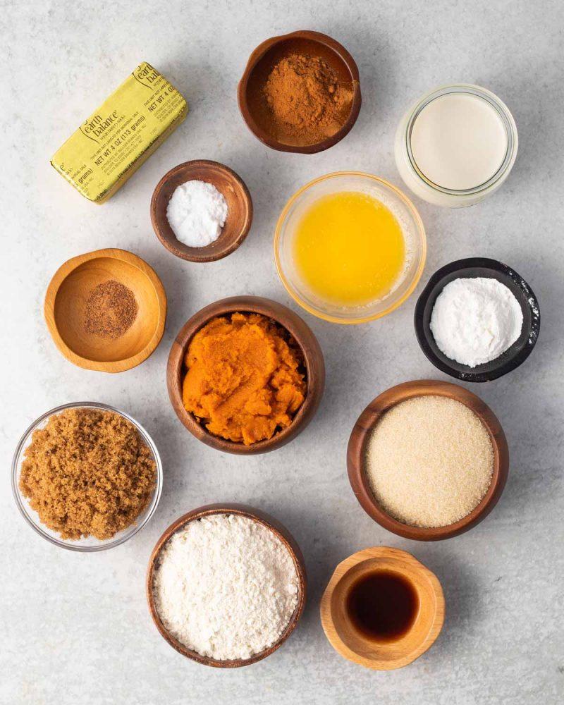 Ingredients laid out on a surface: cinnamon, baking soda, baking powder, vegan butter, oat milk, nutmeg, pumpkin puree, sugar, brown sugar, flour, and vanilla.