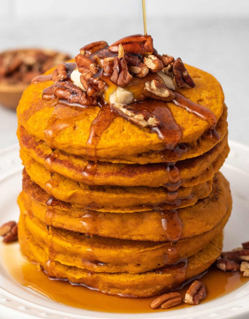 A stack of 6 vegan pumpkin pancakes topped with dairy-free butter, pecans, and maple syrup.