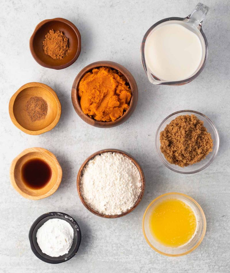 Ingredients laid out on a surface in small bowls: pumpkin puree, cinnamon, nutmeg, vanilla, dairy-free milk, brown sugar, melted vegan butter, baking powder, and flour.