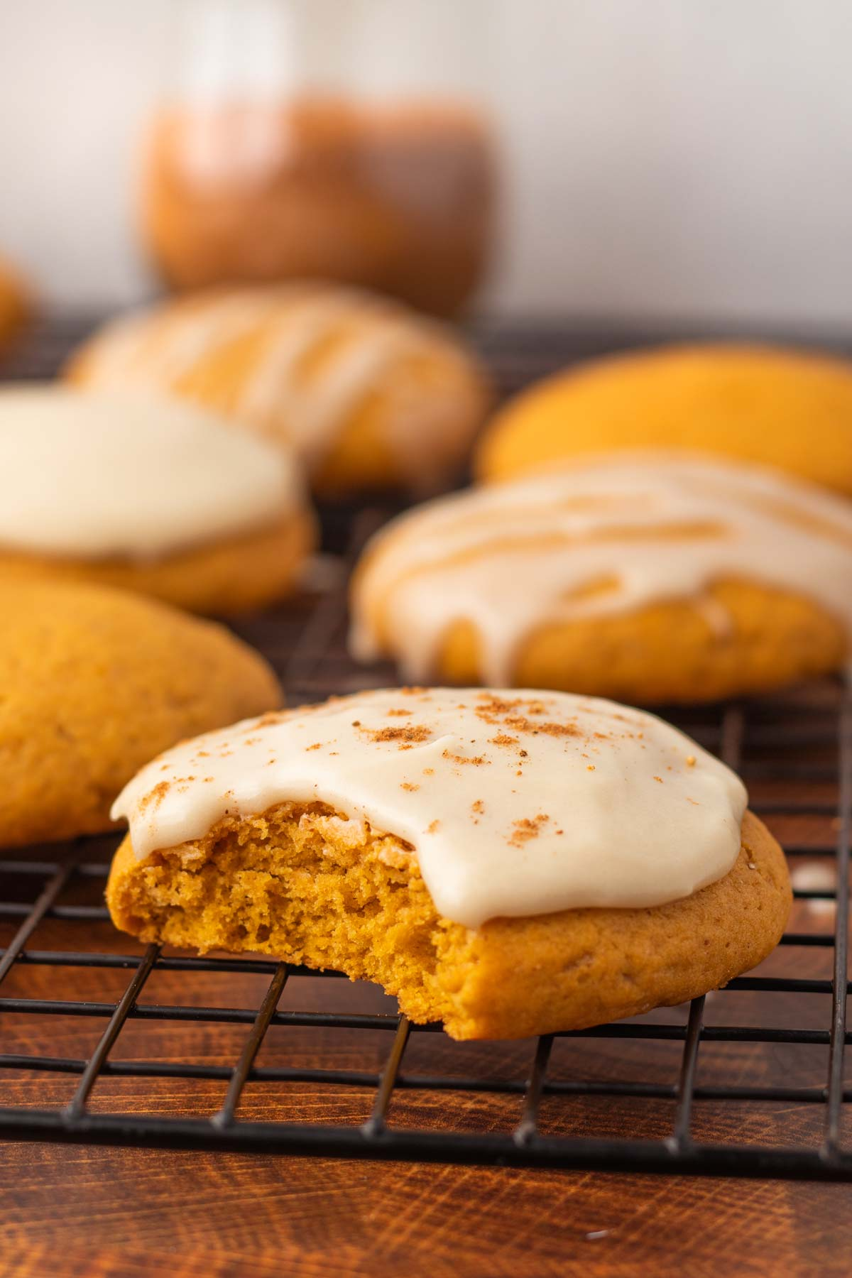 Vegan pumpkin cookies on a cookie rack. The cookie in front is frosted with dairy-free cream cheese frosting and has a bite taken out.