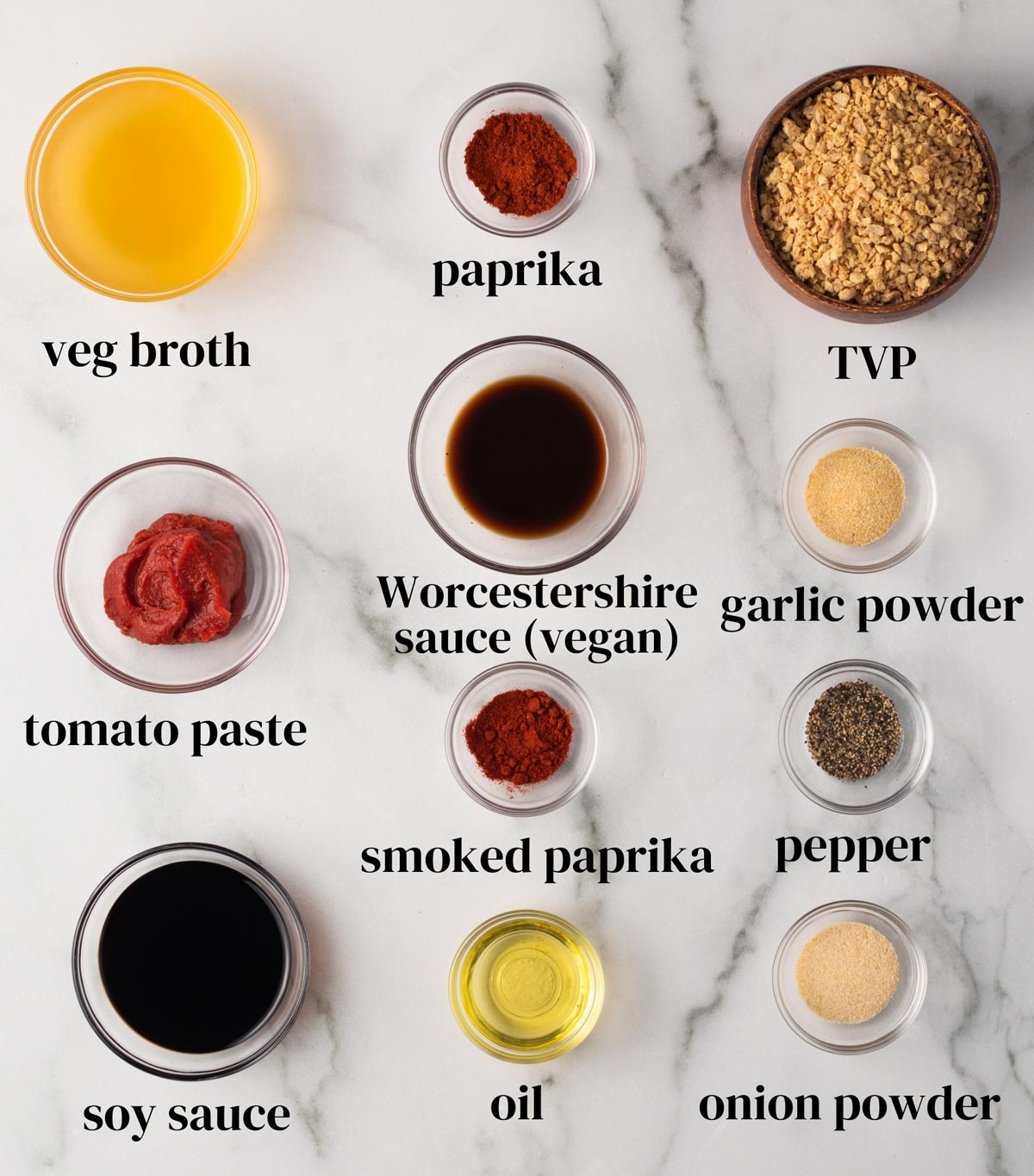 Ingredients for vegetarian ground meat laid out on a surface: vegetable broth, paprika, textured vegetable protein (TVP), tomato paste, vegan Worcestershire sauce, garlic powder, smoked paprika, pepper, soy sauce, onion powder, and oil.