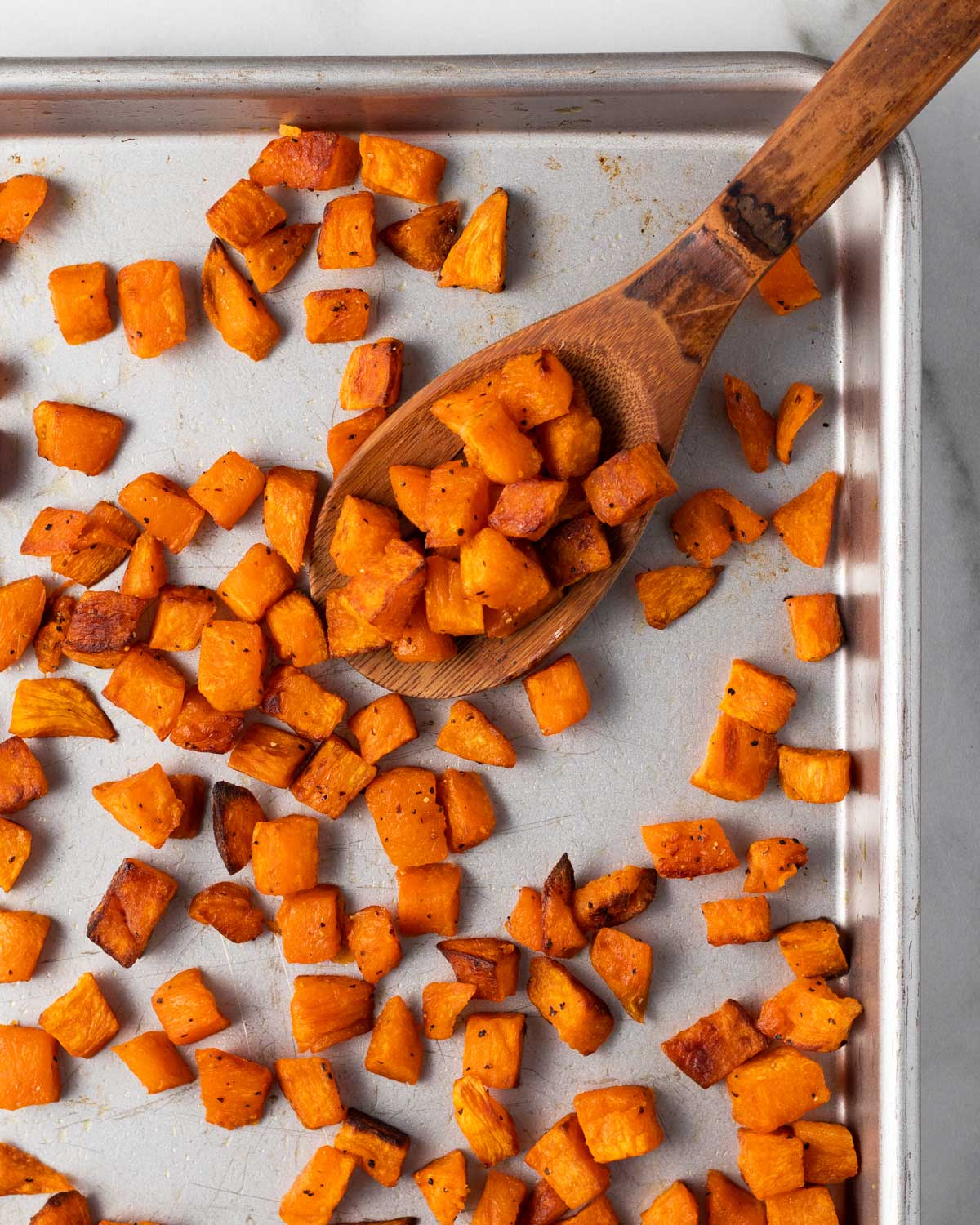 Roasted sweet potatoes with crispy edges on a sheet pan with a wooden spoon scooping some up.