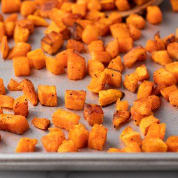A closeup of roasted sweet potato chunks on a baking sheet.