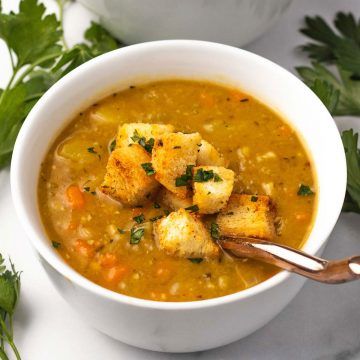 A bowl of vegetarian split pea soup topped with croutons.