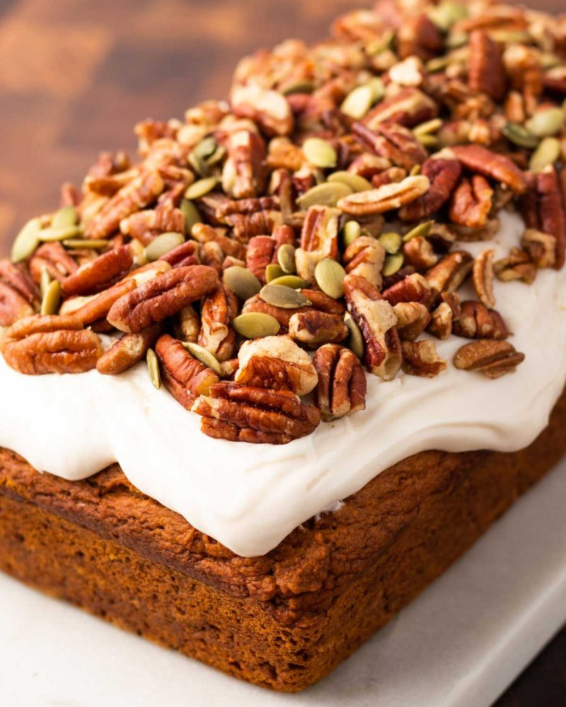 Loaf of vegan pumpkin bread topped with nuts, pepitas, and vegan cream cheese frosting, on a marble serving platter.