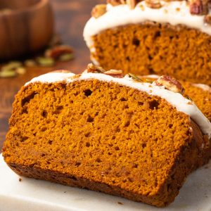 A close up of a piece of pumpkin bread on a marble serving platter.