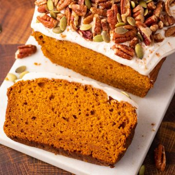 A loaf of pumpkin bread with a slice removed laying flat on a marble serving platter.