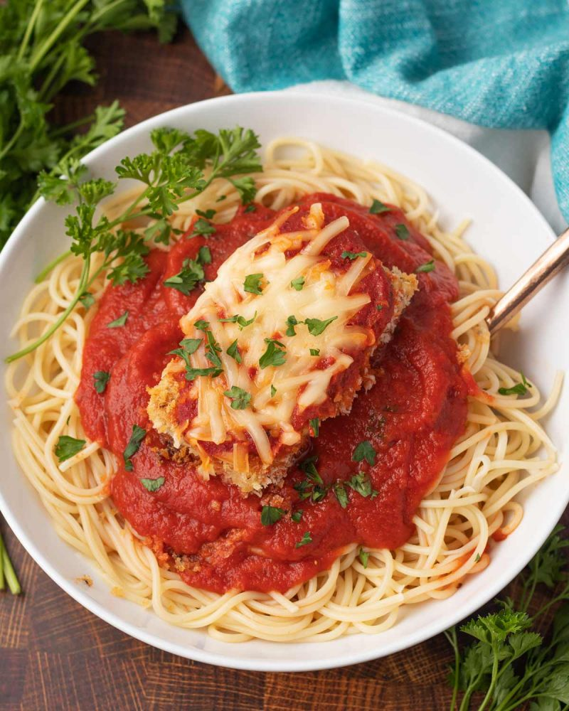 bowl of vegan tofu parmesan with fresh parsley and spaghetti noodles