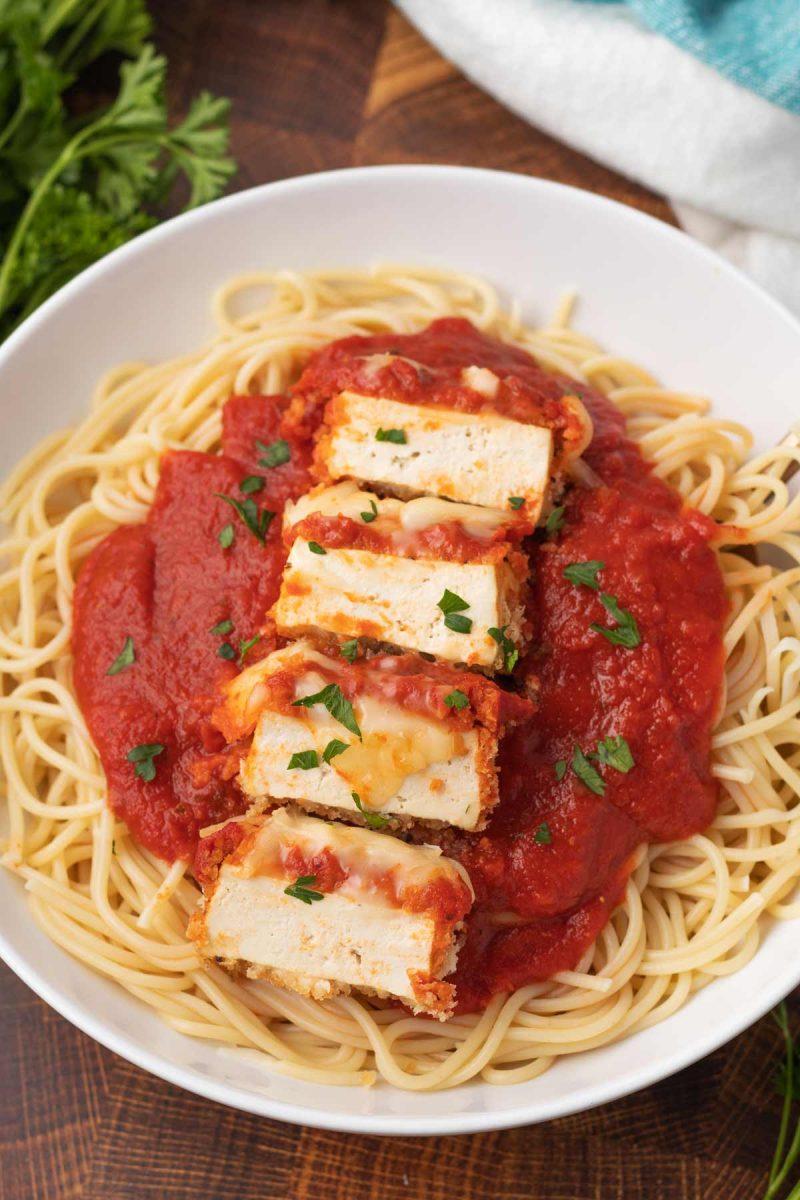 bowl of vegan tofu parmesan with spaghetti noodles and tomato sauce