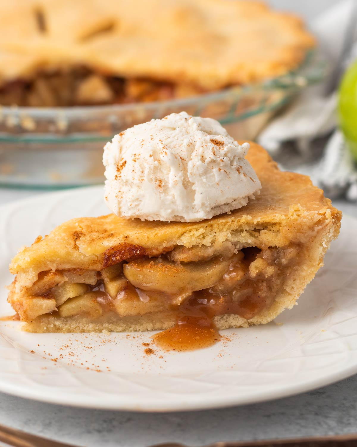 vegan apple pie slice with vanilla ice cream and cinnamon on a white plate