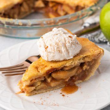 vegan apple pie slice with vanilla ice cream and cinnamon on a white plate