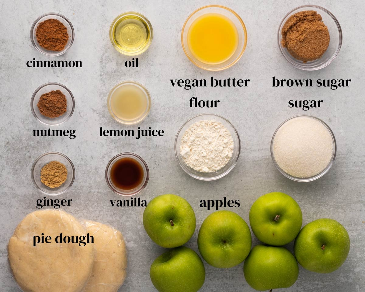 Ingredients needed to make apple pie, including apples, pie dough, cinnamon, and more.
