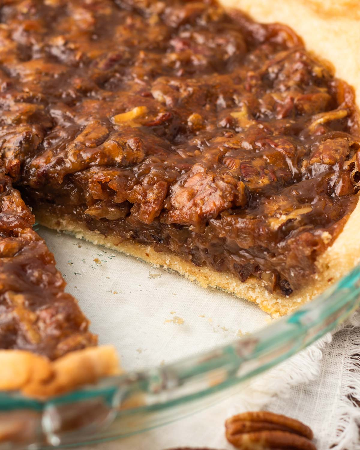 vegan pecan pie with a slice removed from a glass pie plate