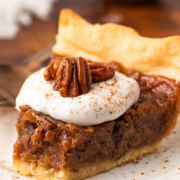 slice of vegan pecan pie with coconut whipped cream