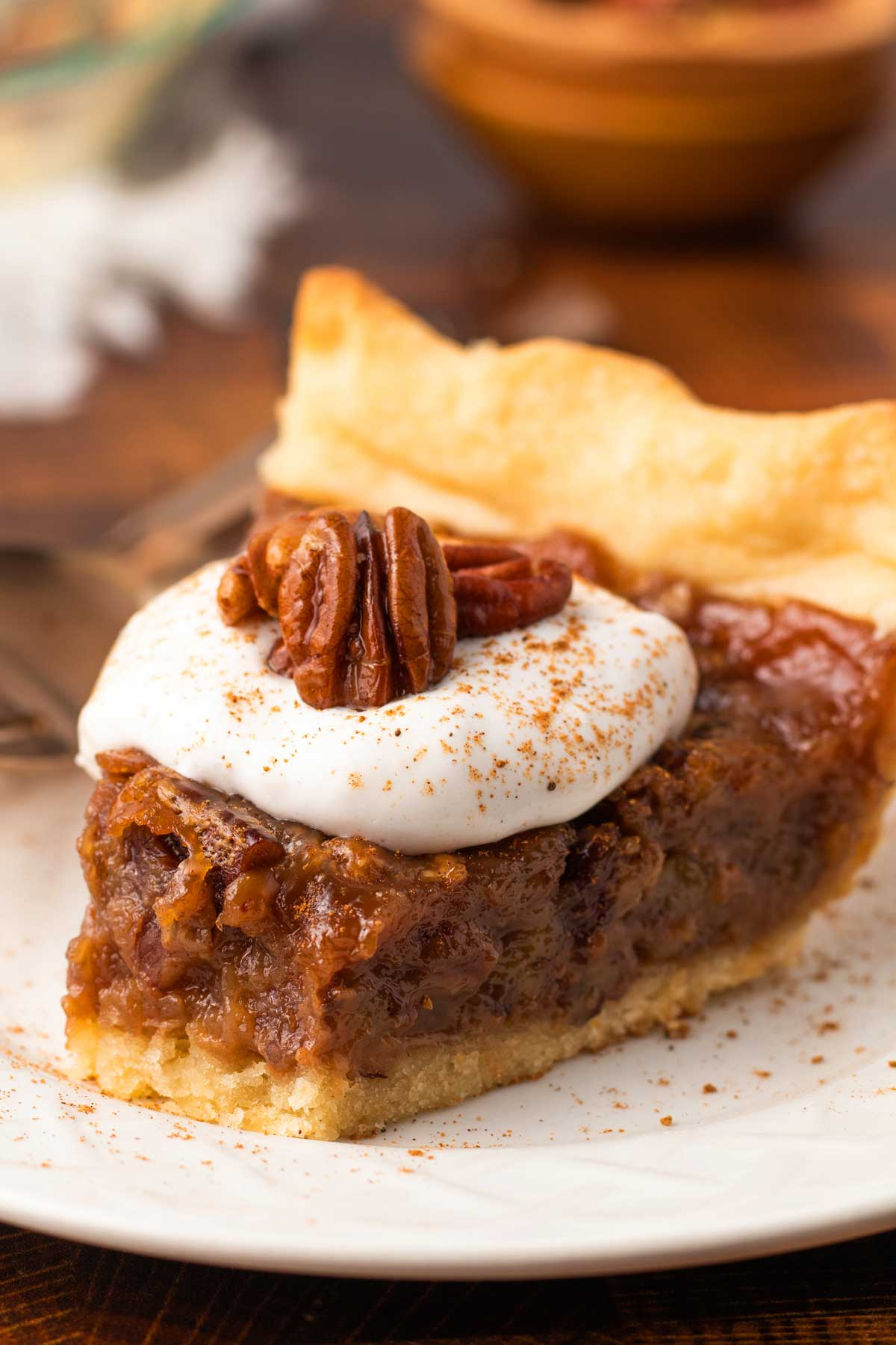 slice of egg-free pecan pie with coconut whipped cream and cinnamon on a plate