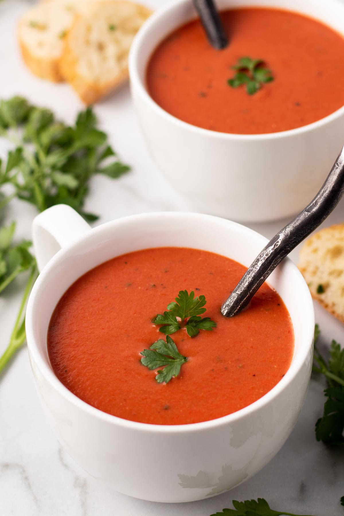 Two white bowls filled with tomato soup made with tomato paste.