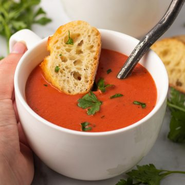 A bowl of vegan tomato soup with a baguette slice.