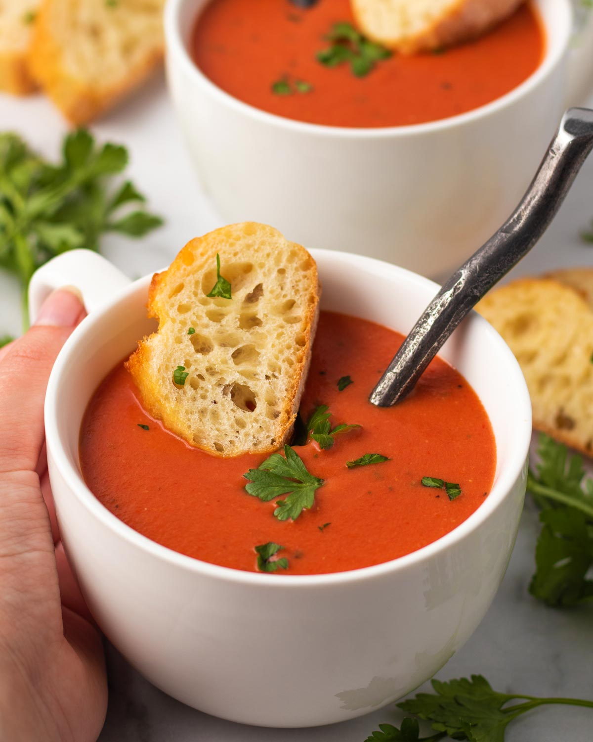 A large mug of vegan creamy tomato soup with a baguette slice, topped with fresh parsley.