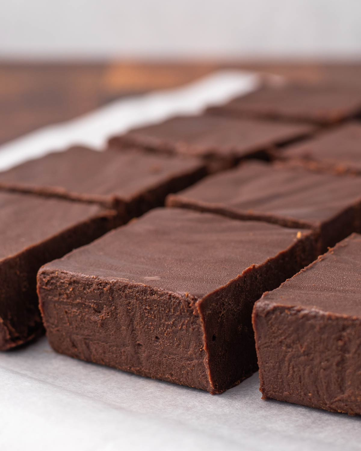 Fudge sliced into squares on parchment paper.