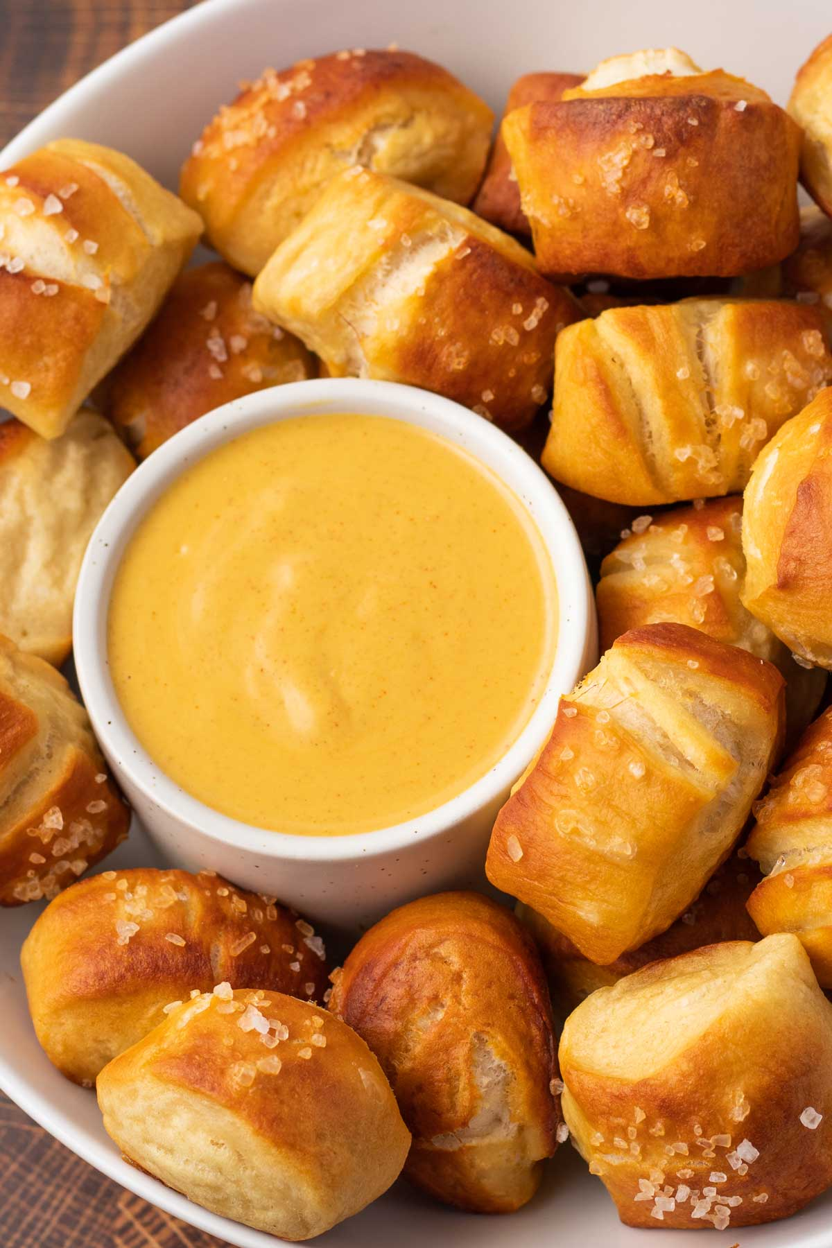 close up on a bowl of vegan cheese dip with pretzel bites for dipping.