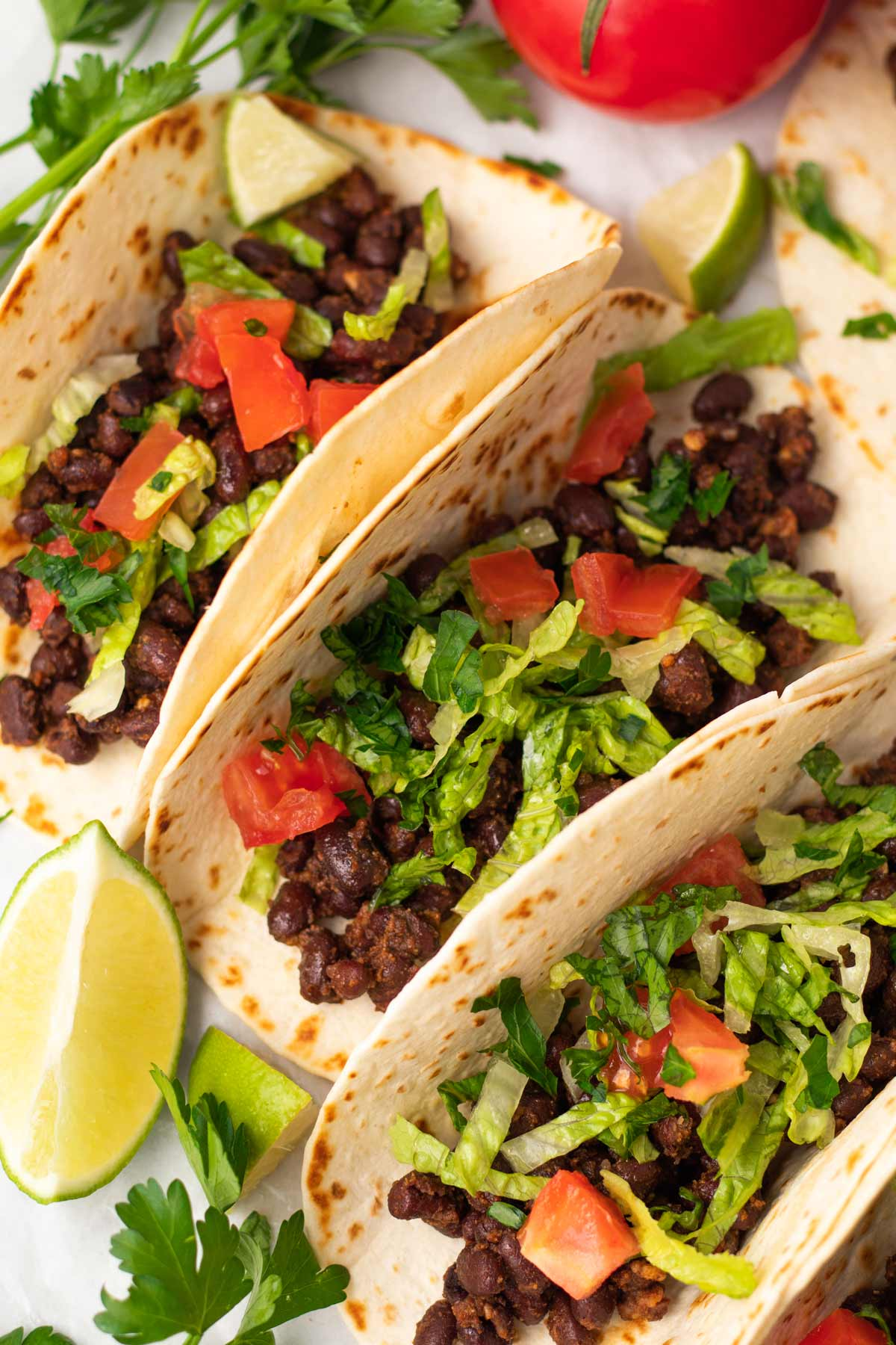 close up on vegan black bean tacos with lettuce, tomato and cilantro in soft tortillas