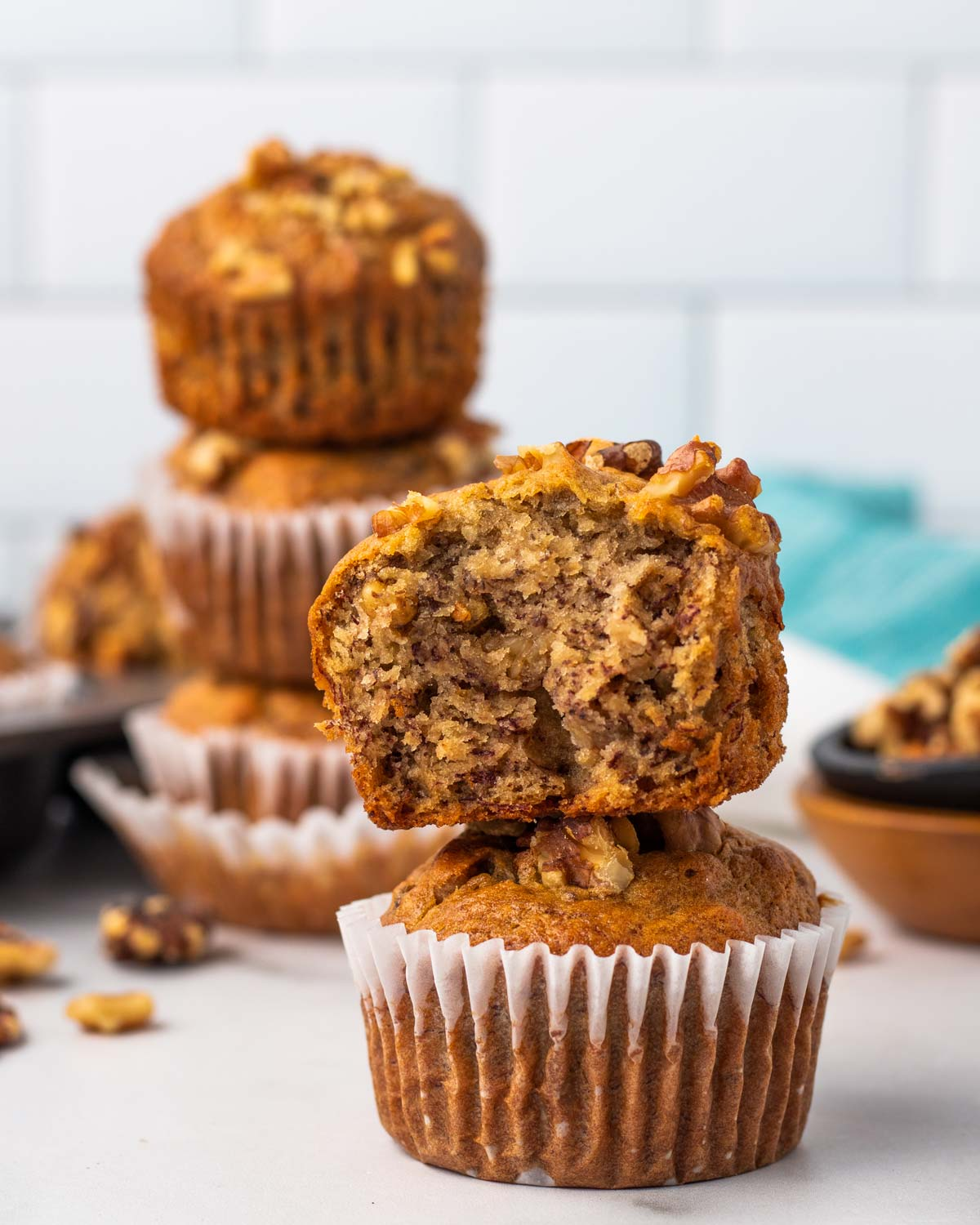 close up on a stack of two walnut muffins with one cut in half to show the texture
