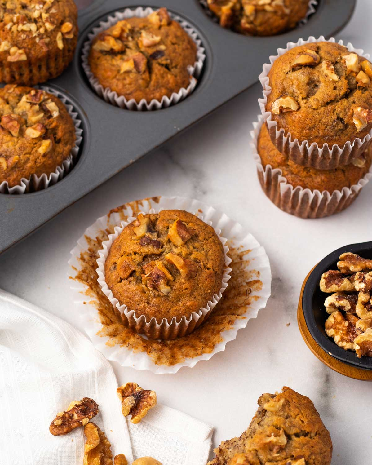vegan banana nut muffin with the wrapper removed on a marble board