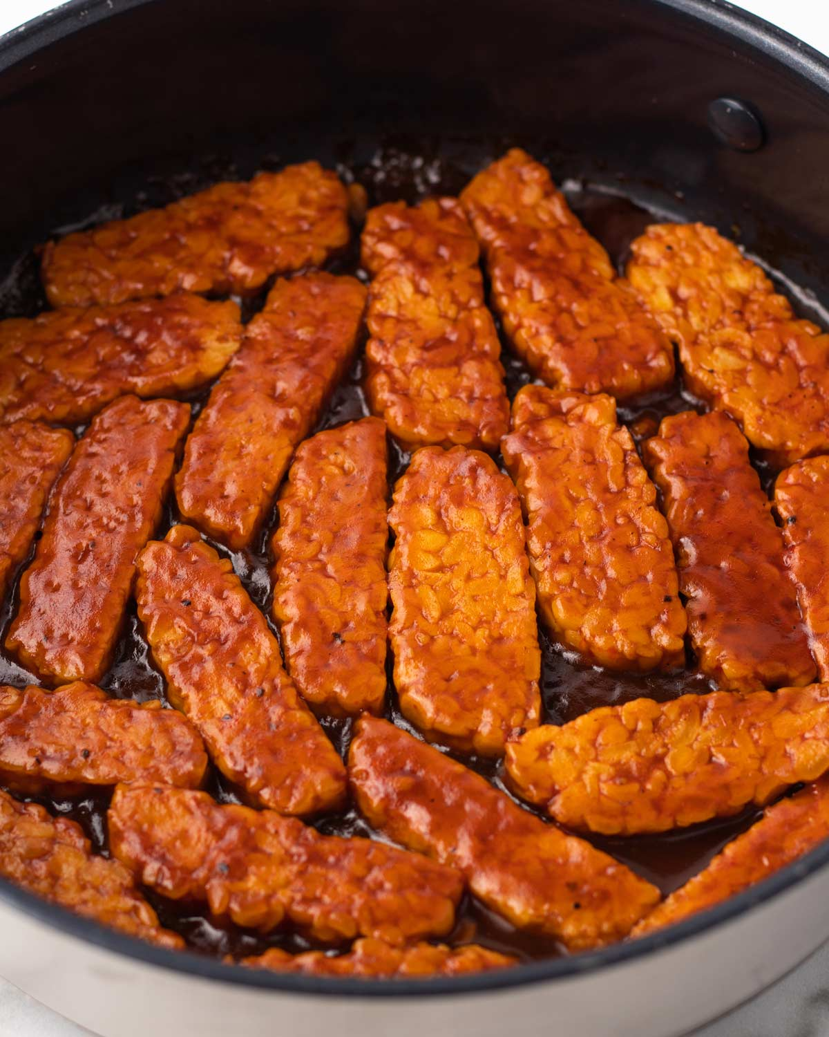 close up of tempeh cooking in bbq sauce.