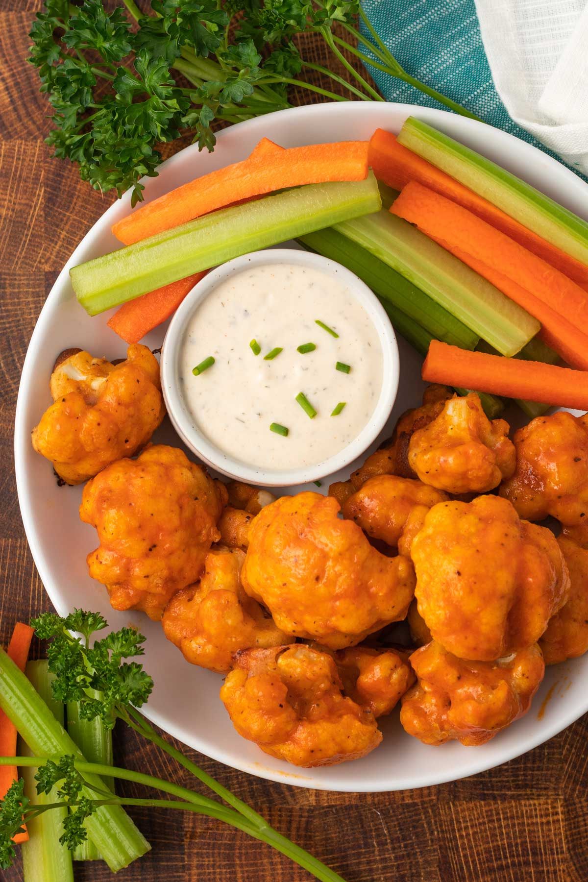 A plate filled with buffalo cauliflower wings, celery, carrots, and a dish of vegan ranch.