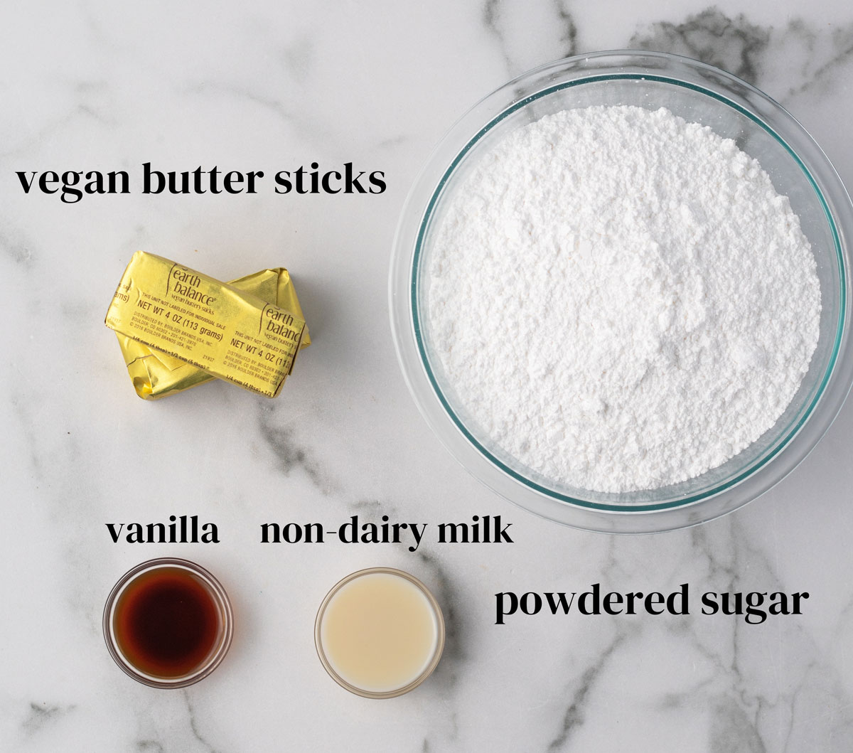 Ingredients for vegan buttercream frosting: powdered sugar, dairy-free butter, oat milk, & vanilla.