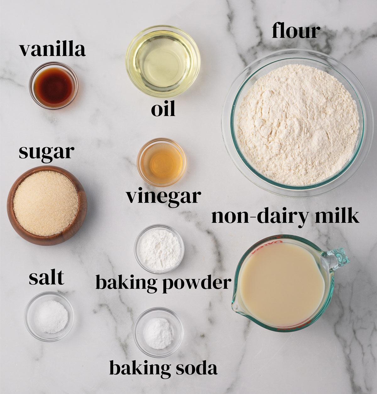 overhead of all of the ingredients for vegan vanilla cake: flour, milk, sugar, vinegar, vanilla