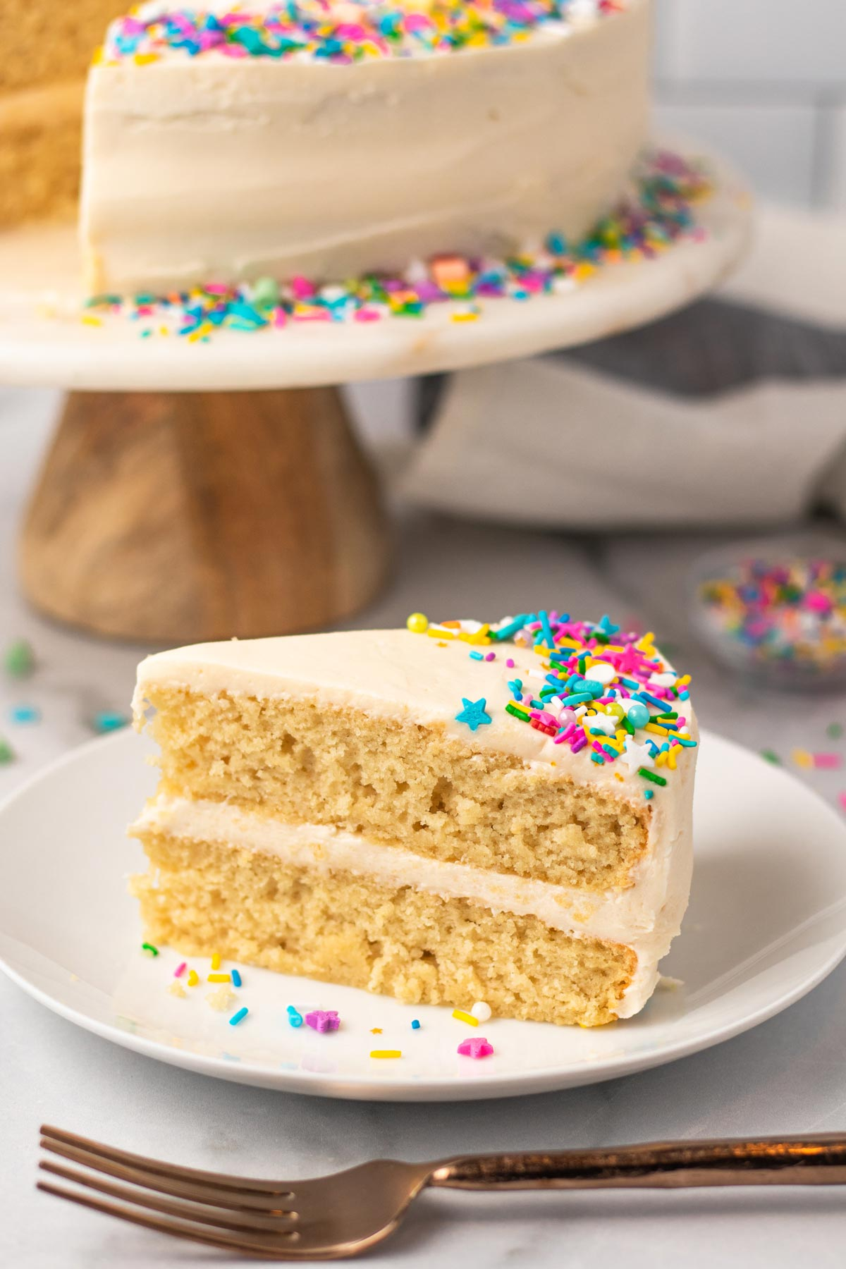 slice of vegan vanilla cake in front of the whole cake on a cake stand in the background