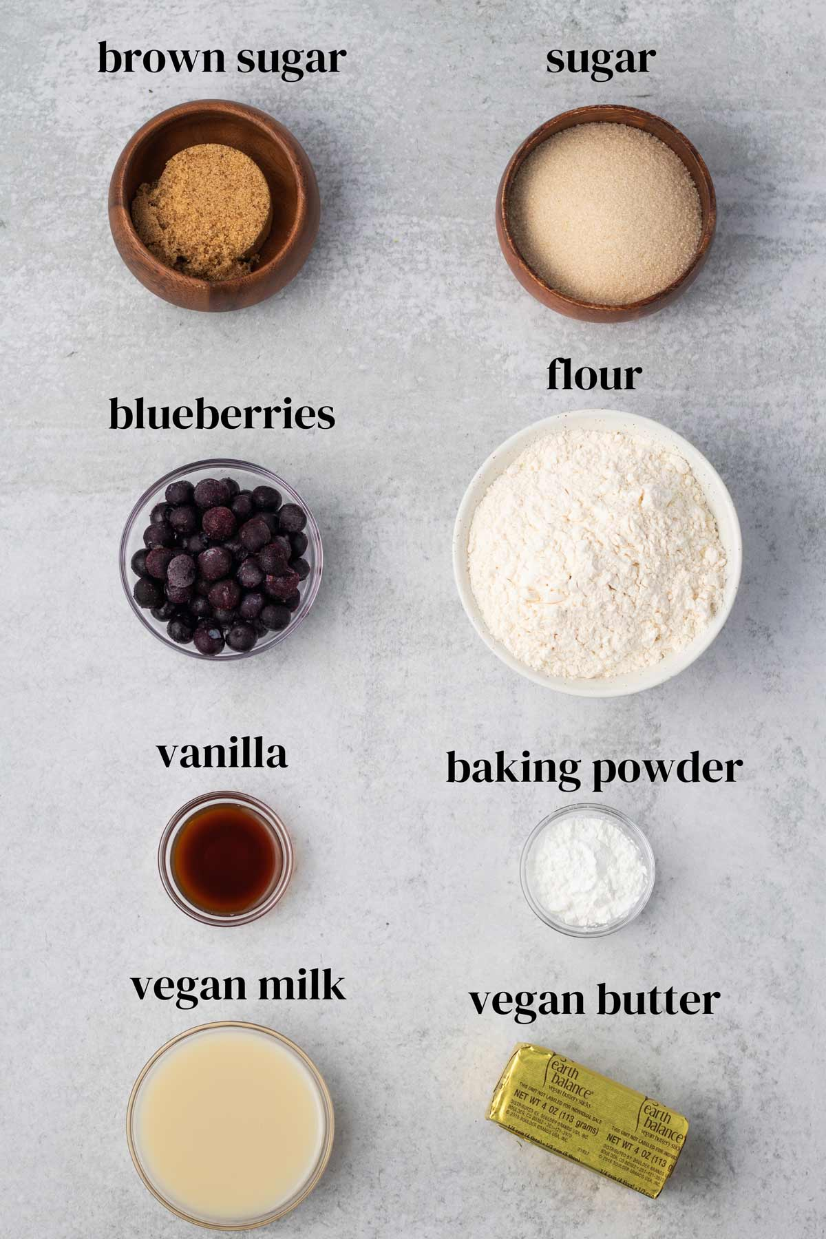 overhead of all of the ingredients to make vegan blueberry muffins in small bowls