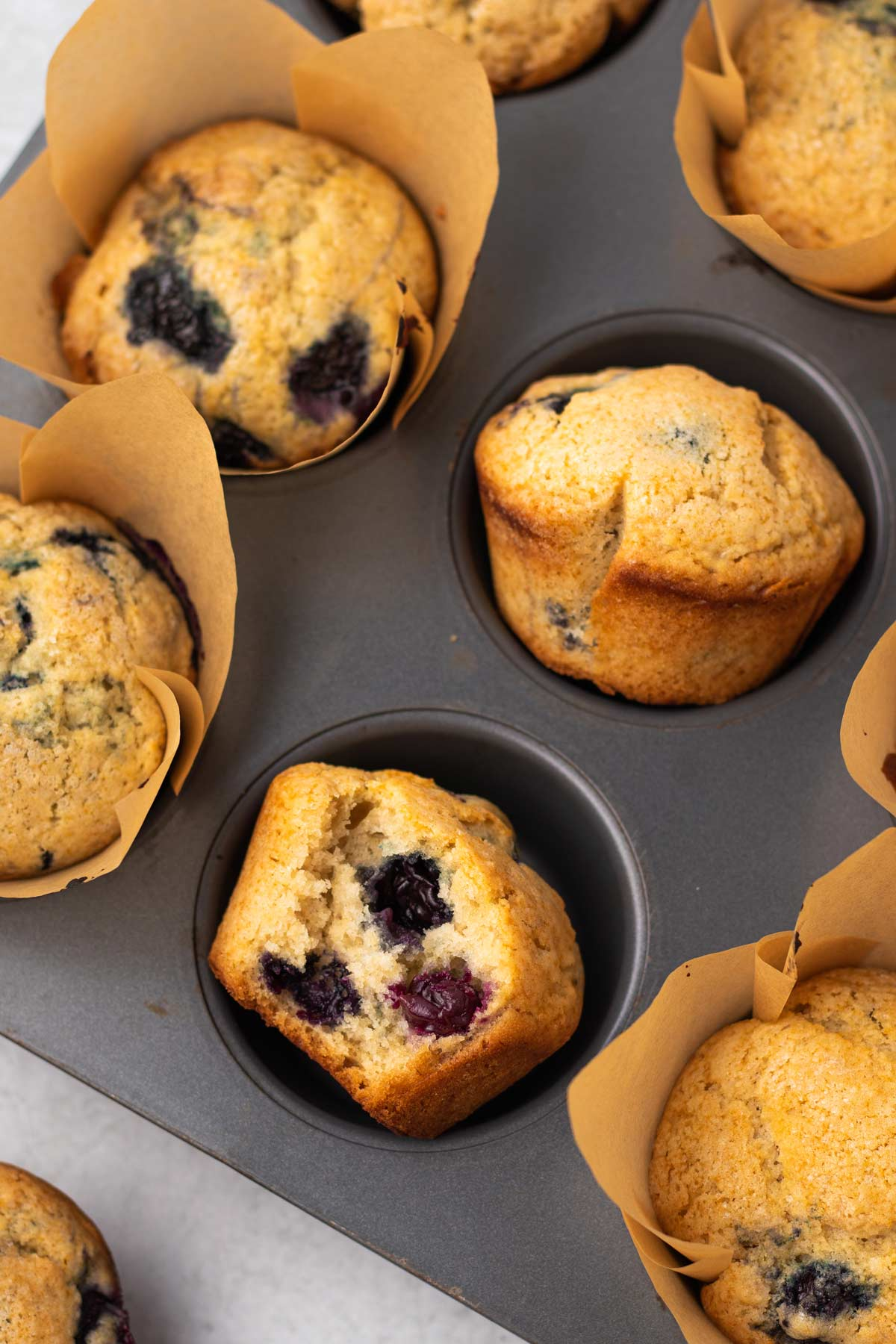 close up on a vegan blueberry muffin in the muffin tin with a bite removed