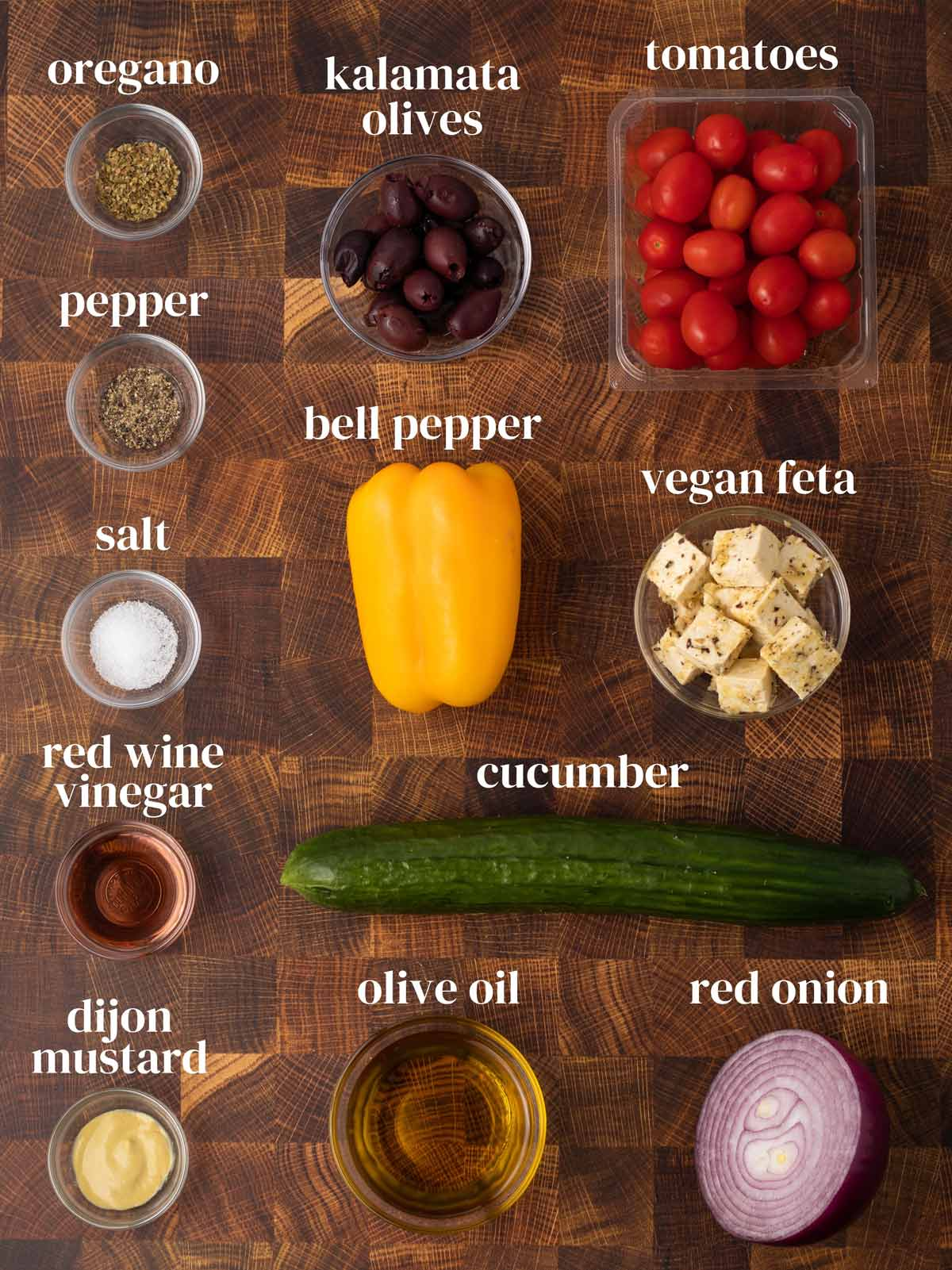 Ingredients for the salad including kalamata olives, tomatoes, oregano, cucumbers, and olive oil.