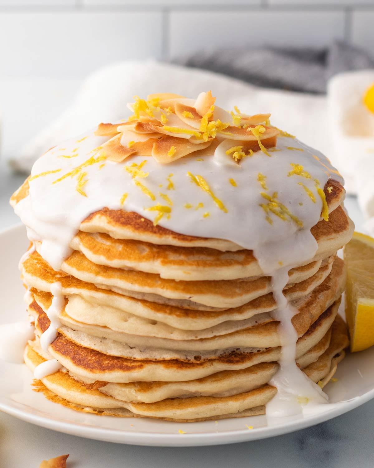 stack of lemon coconut pancakes with glaze, coconut chips and lemon zest on top