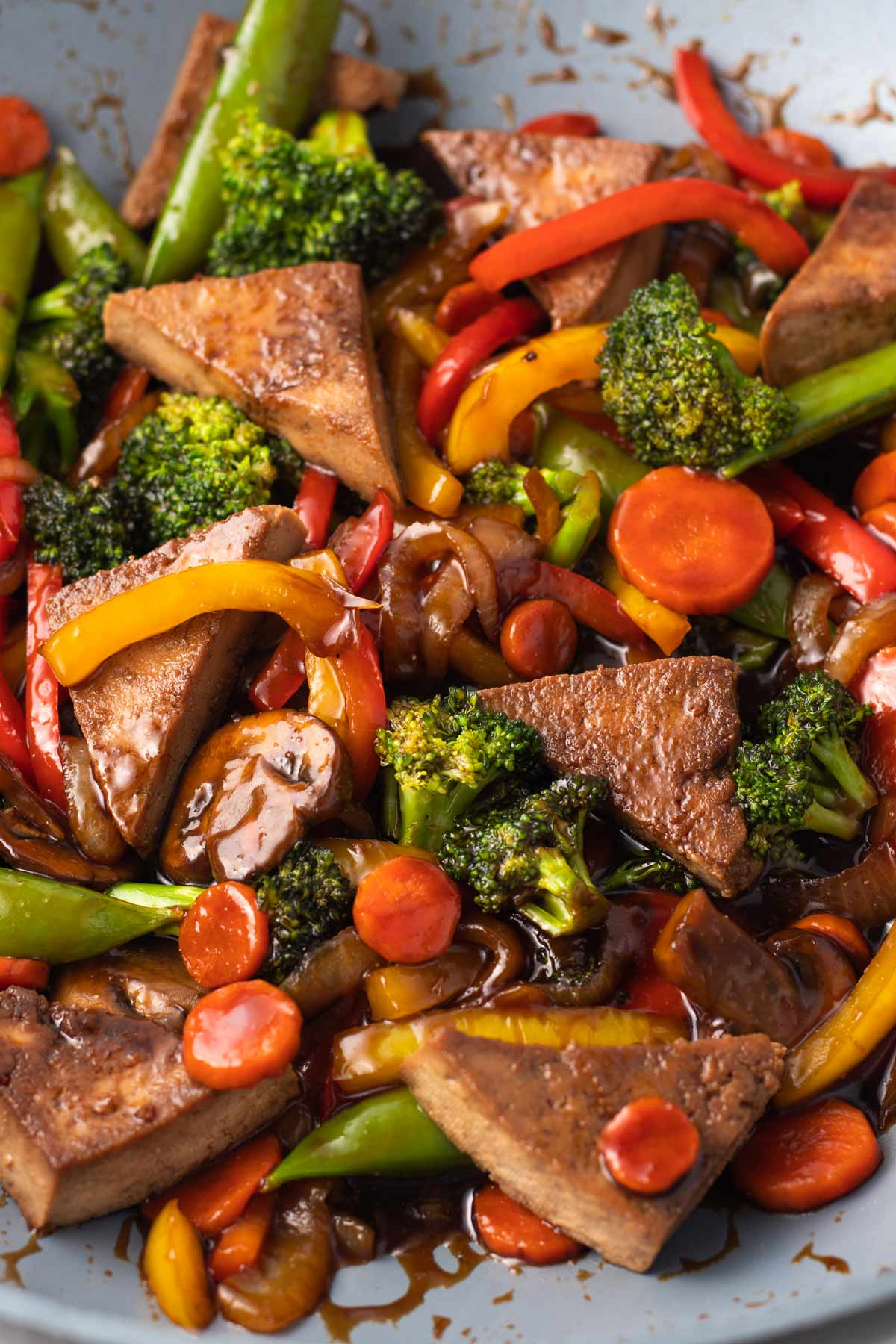 close up on teriyaki tofu stir fry in a wok with colorful vegetables